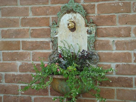 Antique French water font.  This is gorgeous in the front flower bed! My hubby added the faucet and hung this on the front of the house. So pretty!
