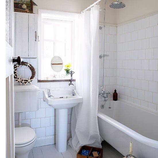 The all white palette in this bathroom creates a fresh, clean look. Painted floorboards, a tongue and groove-style wall cupboard and a starfish wreath add a nautical flavour