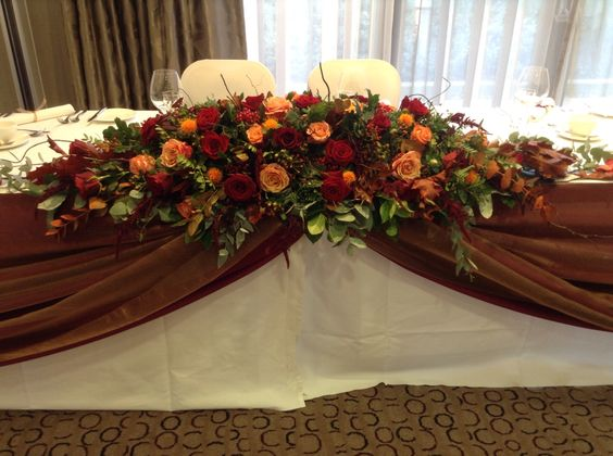Rich autumn reds, golds, and russets using berries, rose hips, hypericum, acorns, deep red roses, cherry brandy roses,  amarathus  top table wedding decoration. www.thefloralartstudio.co.uk