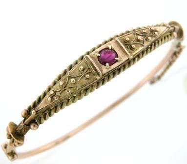 Victorian circa 1880, Etruscan revival 9k yellow gold hinged bangle set with a cabochon ruby and accented with granulated bead work.