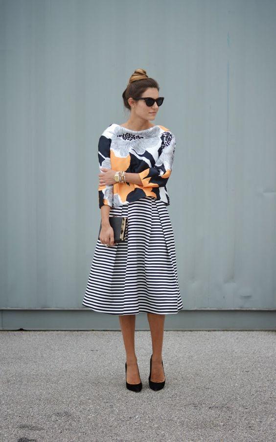 inspiração street style para um mix de estampas com blusa de manga longa floral, saia mídi listrada, scarpin preto, clutch preta e óculos gatinho preto: