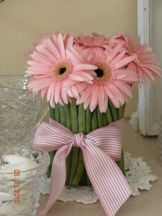 round jar with green beans held by rubberband... ribbon covers rubberband... works great with gerbera daisies!