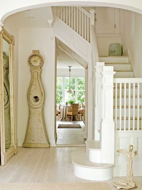 """""""In the foyer, a floor mirror and a Swedish clock both stand 8 feet tall, accentuating the ceiling height."""" Mora clock and mirror: Tone on Tone. Loi Thai's early-1900s four-level Edwardian townhouse in Bethesda, Maryland. Interior design by Loi Thai, Tone on Tone. 