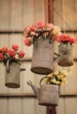 hanging old watering cans with flowers: