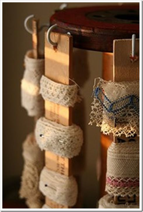 Paint sticks with ribbon and trim wound around and pinned.  Creative and a great way to keep them organized!