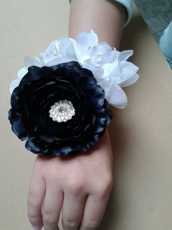 homecoming flower wristlet with a rhinestone center and attached to a rhinestone bracelet. $18.00
