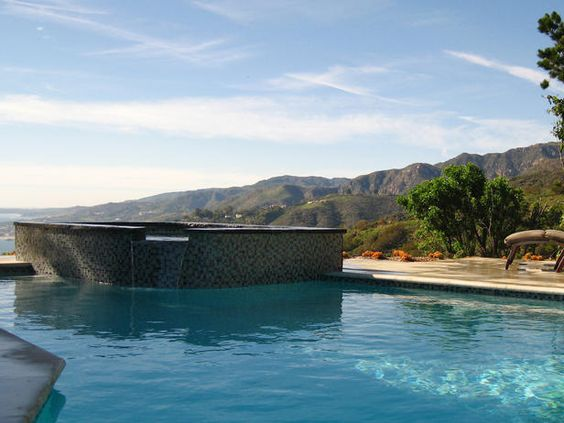 A tiled aboveground spa boasts a spillover water feature into the turquoise pool.
