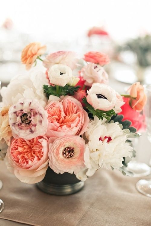 Centerpiece with pink ranunculus garden roses peonies and