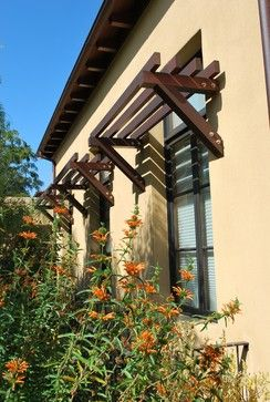 Awnings typically manage to work double-duty, adding curb appeal while also filtering the sunlight that comes into your home and protecting your windows from the elements. Traditional cloth awnings come in a variety of sizes and styles, but a wood awning is striking!