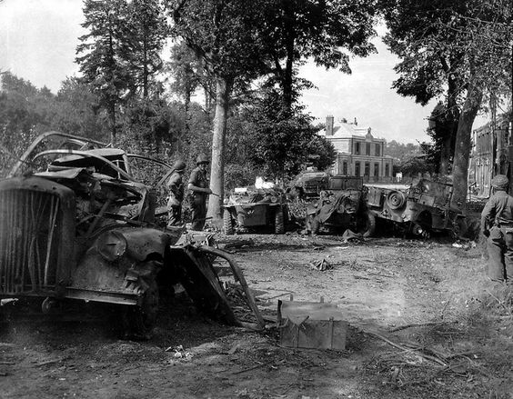 Trois soldats américains contemplent des épaves de véhicules à Mortain dans le fond la gare de Mortain-Le Neufbourg, le 12 août 1944, au premier plan au sol sur la caisse, le triangle de signalisation qui devait être fixé sur le toit du camion.