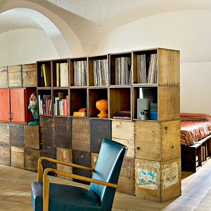 Vue de la chambre d'amis entourée de bois et de demi cloisons    Les casiers en bois chinés sont partout : ils structurent l'espace, font office de sommier et de tables de chevet. Fidèle à son principe de chineur invétéré, l'architecte Alessandro Capallero a aussi trouvé les fauteuils en cuir bleu dans la rue.