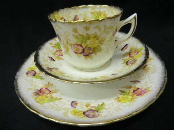 Edwardian tea trio by Stanley china Cup with slightly flared lip pinched loop handle and scalloped rim Generously gilded with sponged gold