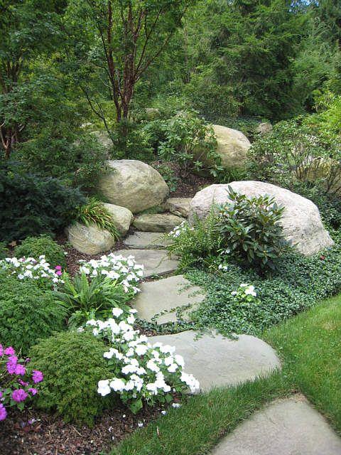 Caminho de pedras grandes (lindo), grama bem cuidada e algumas flores.