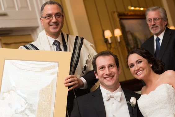 Rabbi Lev Herrnson displays a full endorsed ketubah at the signing ceremony, just before the wedding under the chuppah.