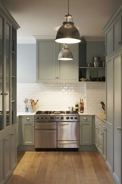 white subway tile backsplash :: muted moss green cabinets :: pendant ceiling light :: range oven :: wooden floors: