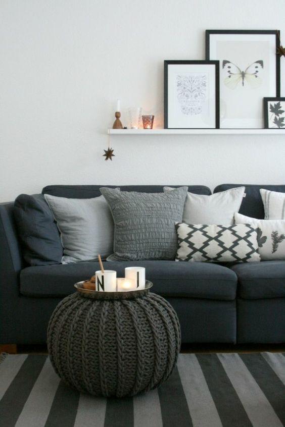 Dunkelblaue Couch mit vielen Kissen in Grautönen, grauer Strick ...