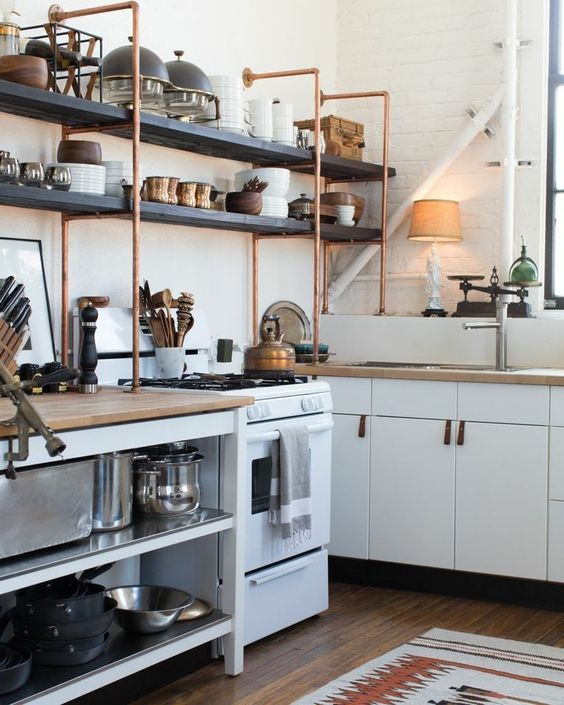 Kitchen shelves built from copper pipe. Gorgeous! The kitchen is actually Ikea with self made leather handles. The LA home of Kristan Cunningham and Scott Jarrell.