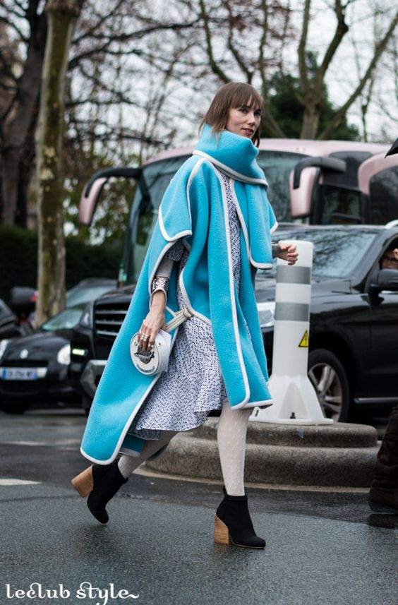 Womenswear Street Style by Ángel Robles. Anya Ziourova wearing an electric blue coat with white tighs and black ankle boots at Dior Haute Couture show, Paris. Fashion Photography from Paris Fashion Week.