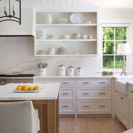 Gorgeous white serene kitchen design with white cabinetry, open shelves, wood floors, and beadboard ceiling.! #kitchendesign #kitchendecor #whitekitchen #whitedecor #shelves #beadboard #serene