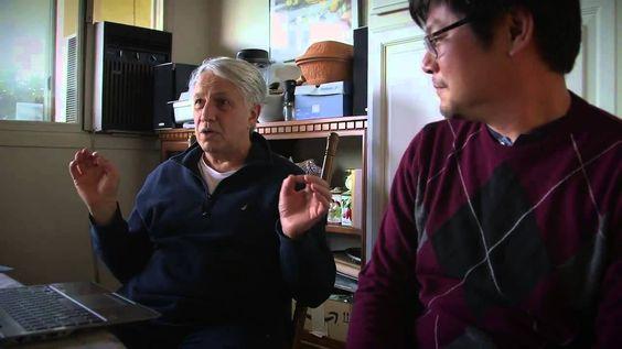 """El Profesor Asistente Chao-Lin Kuo sorprende al Professor Andrei Linde con evidencia que soporta la teoría de inflación cósmica. El descubrimiento, hecho por Kuo y sus compañeros en el experimento BICEP2, representa las primeras imágenes de ondas gravitacionales, u ondas en el espacio-tiempo. Estas ondas han sido descritas como """"los primeros temblores del Big Bang"""""""