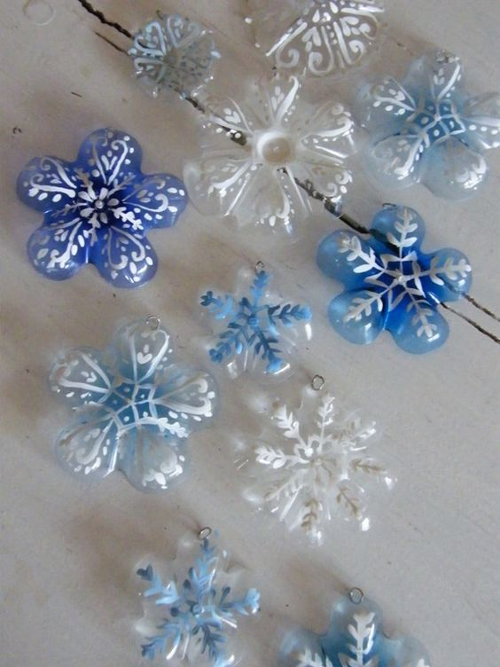 Snowflake plastic ornaments made from the bottoms of pop & water bottles!  Wait, do I see flowers painted in pinks and yellows and reds and purples?  www.handsonaswegr...  #snowflake #ornaments #water #bottle #bottoms #flowers #plastic #craft #diy #create