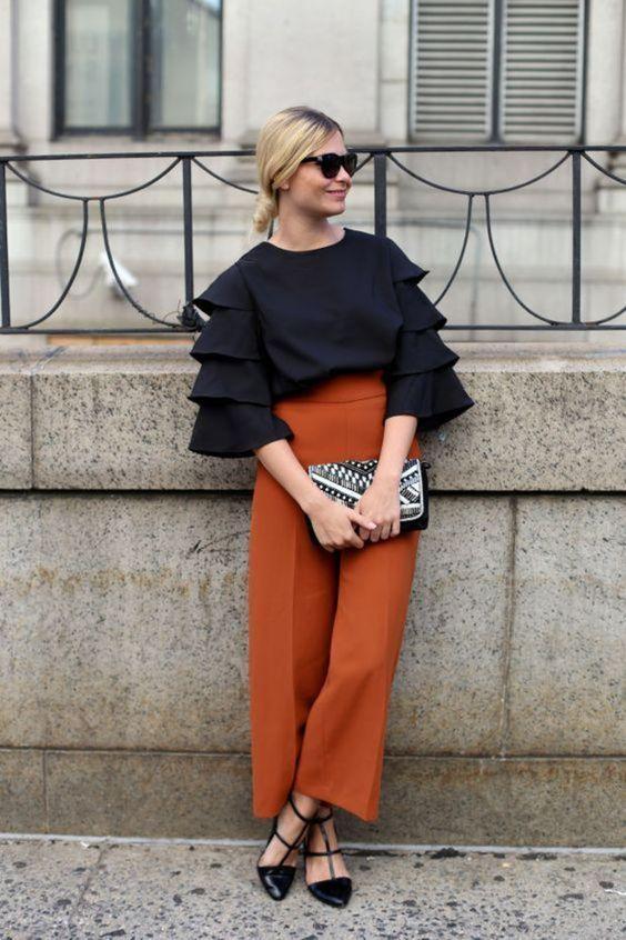 Camisa preta com babados, calça de alfaiataria laranja, sapatilha de bailarina preta