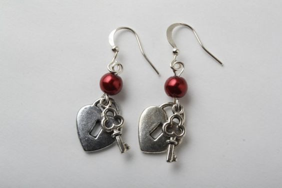 Cute Tibetan silver earrings. A silver heart shaped locket and key dangles below a red glass pearl. Ear wires are in silver. These earrings measure