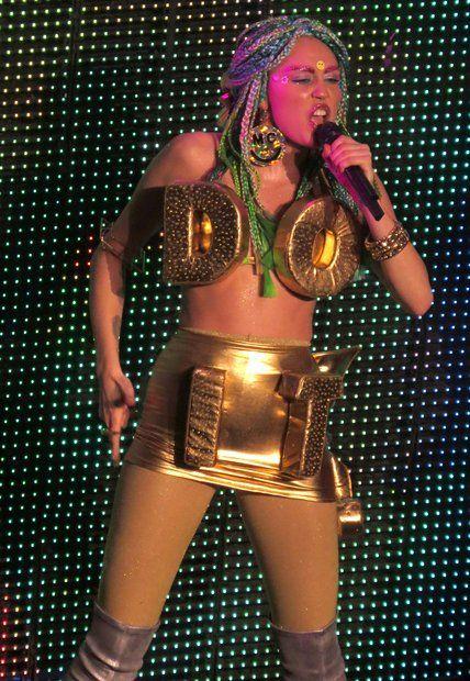 """Fashion: """"Do it"""" lauten die zwei Worte, die riesengroß über Miley Cyrus' goldfarbenem Gladiatoren-Space-Look prangen. """"Mach es einfach"""", muss auch sie sich gedacht haben, als sie sich dazu entschied, mehr Fake-Haar als Stoff zu tragen."""
