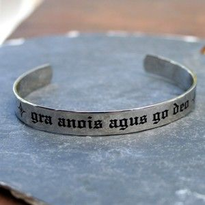 "Our Gra Anois Agus Go Deo Cuff in gaelic means ""Love Now and Forever."" this handsome Gaelic cuss in stainless steel shows your true feelings. This Irish cuff bracelet is made of stainless steel and has the words 'gra anois agus go deo' in black lettering and the English translation, 'Love Now and Forever', is secretly inscribed on the inside. It's the perfect little secret between you and him."