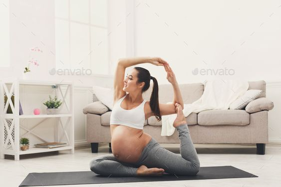 Happy pregnant woman training yoga in camel pose by Prostock-studio. Happy pregnant woman training yoga in camel pose at home. Motherhood, active pregnancy, happiness, training, yoga con...#yoga, #camel, #pose, #training