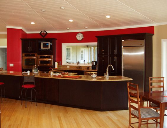 cherry red wall behind rich espresso cabinets in a deltec