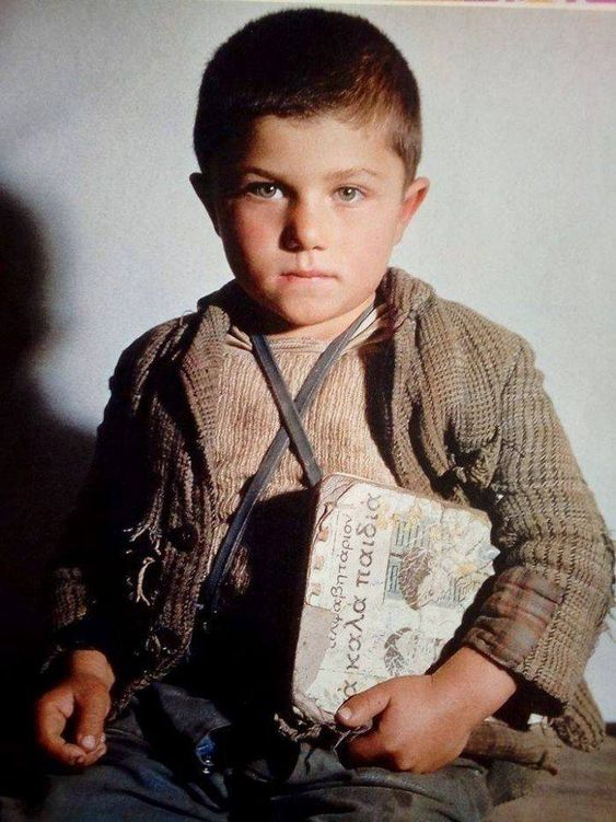 """Ελλάδα 1951 φωτογραφία Δημήτρης Χαρισιάδης.Με το βιβλίο παραμάσχαλα. Η έγχρωμη φωτογραφία του Δημήτρη Χαρισιάδη.Αυτή την έγχρωμη φωτο του Χαρισιάδη, είναι από το περιοδικό """"Εκλογή"""" του 1954. Το Αλφαβητάριο αυτό """"Αλφαβητάριο τα Καλά Παιδιά"""", το Αλφαβητάριο του Ρήγα, εκδόθηκε το 1949 μέχρι το 1954. Οι λιθογραφικές εικόνες του είναι του Κώστα Γραμματόπουλου και είχε λάβει το πρώτο βραβείο από όλα τα Ευρωπαϊκά αλφαβητάρια σε διαγωνισμό του 1949 στο Λάικεν του Βελγίου."""