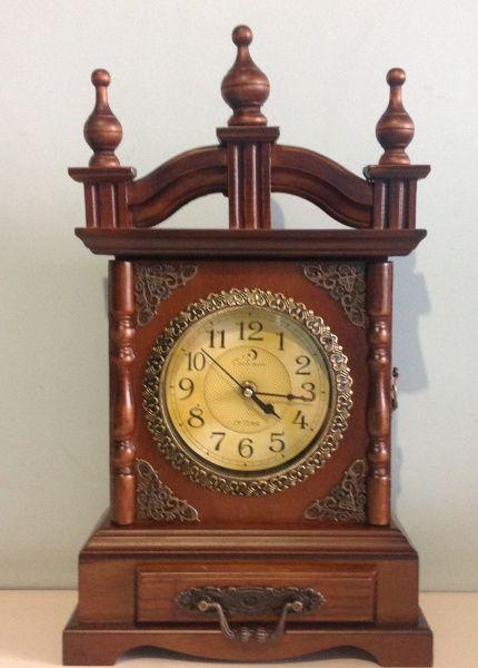 Espetacular relógio de mesa em madeira nobre belamente torneada e detalhes em metal com bordados .