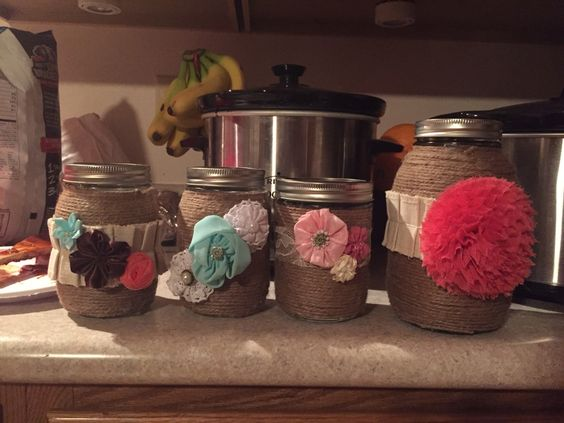 Mason jars wrapped in twine and accented with flowers and lace!
