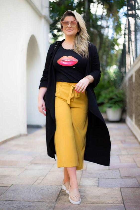 Look de Alice Salazar: Tênis bege, calça amarela, t-shirt preta e casaco preto