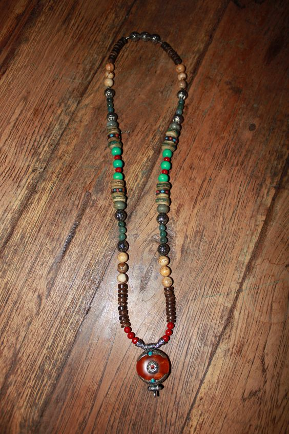 Necklace with coconut shell rondellebeads, picture stone beads, tibetan silver spacer beads, Picasso jasper rondelle beads, yakbone beads, green turquoise wood beads, red Coral beads, green glass beads & a tibetan silver capped amber pendant. 35 € (3)