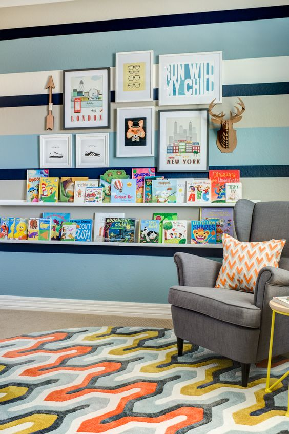 This vibrant gallery wall + library wall is pure perfection for this #bigboyroom! (Fab for a nursery, too.) #kidsroom #librarywall