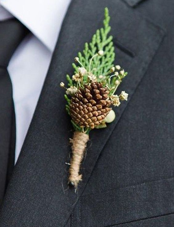 Mini pine cones tied with a sprig of gypsophila make the perfect buttonholes for your winter wedding at Pentney Abbey in Norfolk