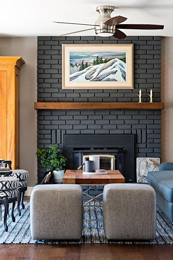Painted brick fireplace with wood mantle the focal point in this farmhouse style living room by Four Blocks South interior design.
