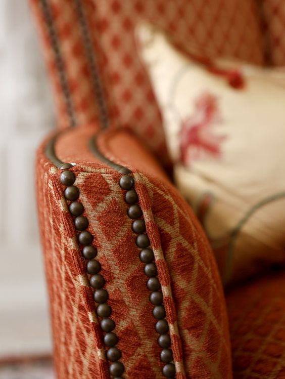 Upholstered chair and arm with deep orange woven fabric and brass nailheads