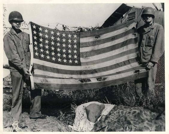 """Original Photo Caption: Stars and Stripes Retaken - Platoon Sergeant Donald C. Bushnell (left) of Nampa Idaho and Captain Louis Wilson Brandon Miss. both Marines hold the first American flag to be retaken from enemy hands on Guam. Below the Stars and Stripes is the first Japanese battle banner to fall to Marines when they landed on the former United States base in the Marianas."""" July 30 1944. Defense Dept. Photo."""