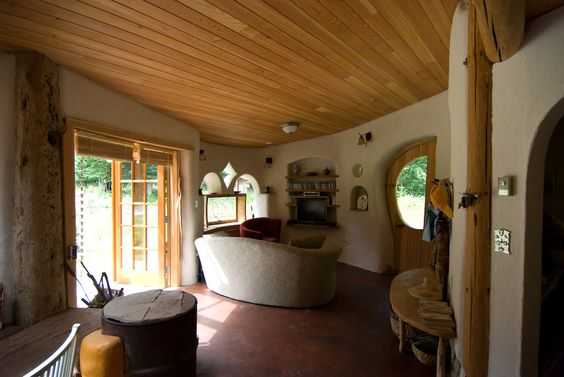 Kate's sitting room includes a cob niche and built in shelves for a television; A rocket stove can be seen in the front left corner.