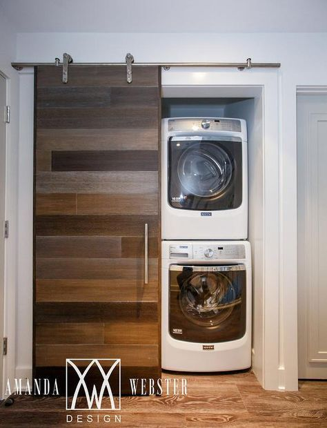 A stunning plank barn door on rails opens to reveal a small hall laundry room fitted with a stacked white front loading washer and dryer.