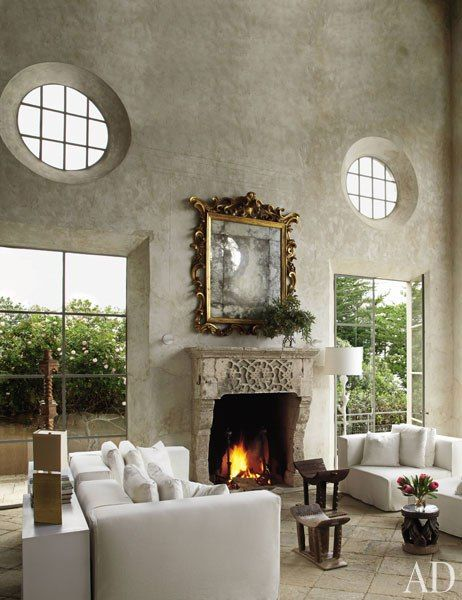"""Antiques dealer Richard Shapiro built a dramatic retreat in Malibu, California, with, he says, """"the look, age, and aura of a very old, windswept structure from the Mediterranean or the Aegean."""" The living room's walls are sheathed in frescoed plaster, complementing a Cypriot fireplace from the 1600s. (April 2011)"""