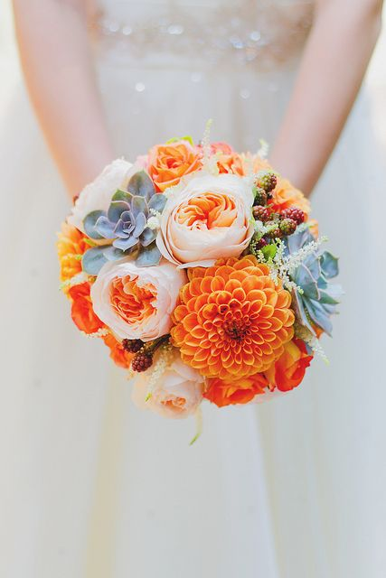 Peonies, roses, and succulents combine to create a dream orange wedding bouquet, perfect for a summer soiree.