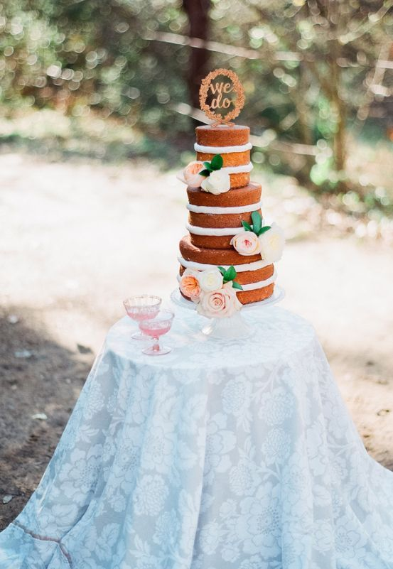 Chic layered wedding cake accented with flowers; Featured Photographer: Marianne Sabado Photography