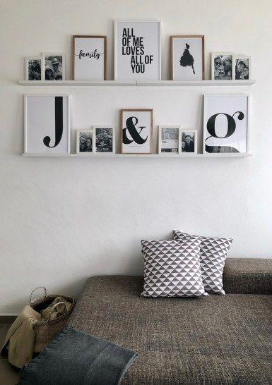 een fotowand maken door planken te gebruiken en daar foto's met verschillende hoogtes op te plaatsen