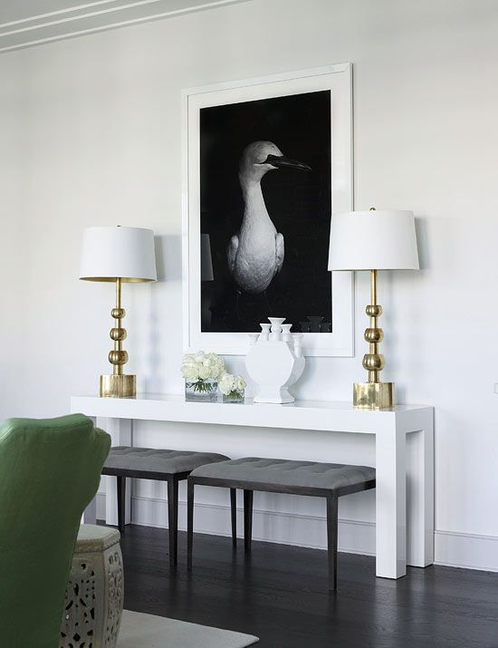 A white Parsons table is used as a console in the living room. The black and…: