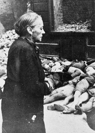An elderly woman stares at the bodies of schoolchildren after an air raid. Braunschweig, 1944.