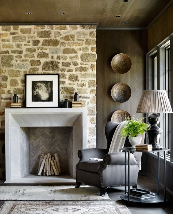 Magnificent living room with stone wall, fireplace, and wingchair. Traditional and classic decor. Farmhouse on Shades Creek. Jeffrey Dungan Architects. #fireplace #stonewall #farmhouselivingroom #jeffreydungan